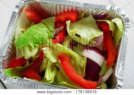 Healthy eating concept. Lunch foil box, take away organic food. Weight loss diet. Fresh vegetable salad from peppers, tomatoes and onions, closeup