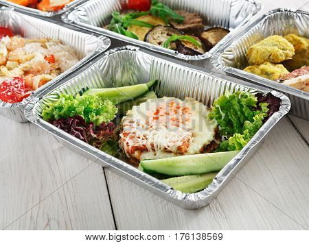 Healthy food restaurant delivery and diet concept. Take away of fitness meal. Weight loss lunch in foil boxes. Pashot poached egg with vegetables and other dishes at white wood