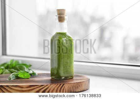 Bottle with oil on wooden stand against window