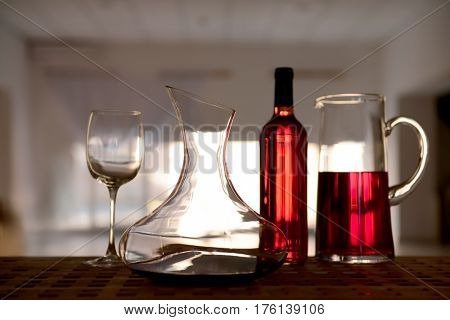 Decanter with red wine and glass on table against blurred background