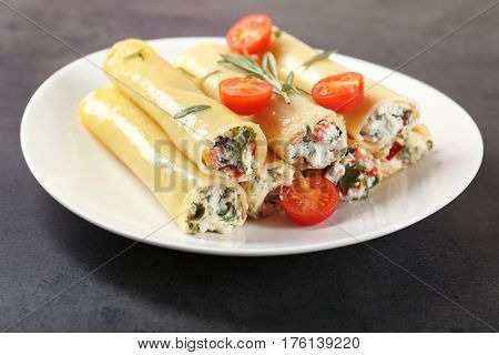 Delicious stuffed cannelloni with cherry tomatoes on plate