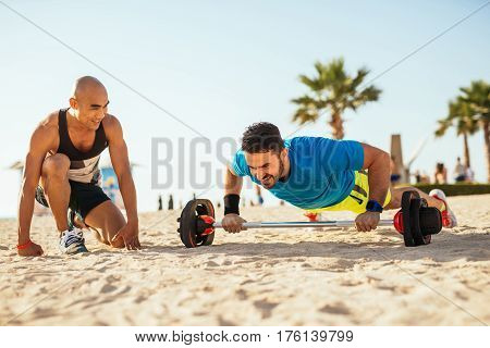 Two man training on the beach in the morning. One of them is doing pushups while the other is cheering him.