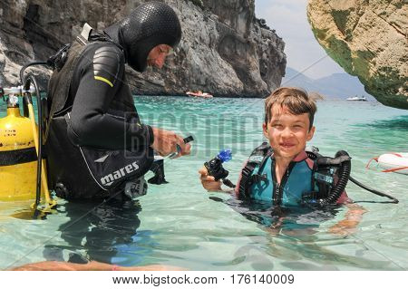 Child Discover Scuba Diving At Cala Mariolu Beach On Sardinia