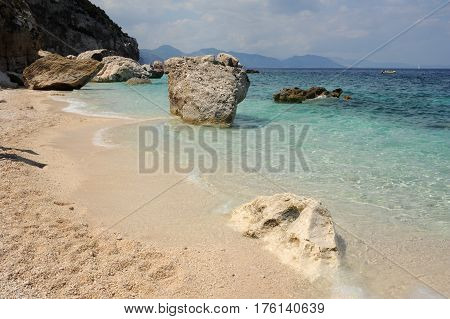 Cala Mariolu, Italy - 28 June 2013: people swimming and sunbathing at Cala Mariolu beach on Sardinia, Italy