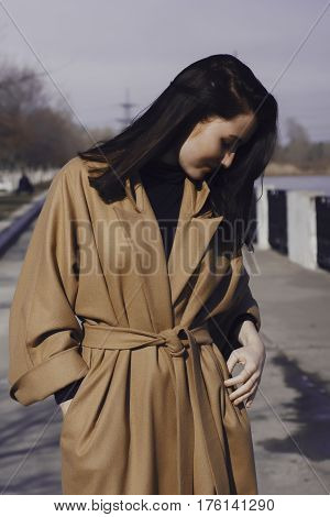 stylish young woman out for a walk. she dressed and looks very fashionable. coat of beige (camel) color and black turtleneck. beautiful woman and looking down.