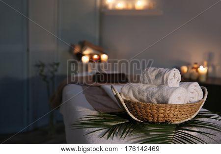 Spa towels in wicker basket on massage table