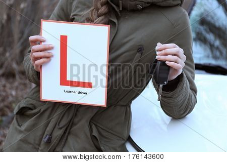 Happy young woman with learner driver sign standing near car outdoors, closeup