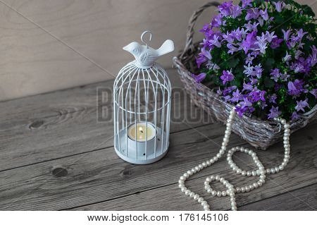 Little white candlestick. Wicker basket with Campanula portenschlagiana and beautiful white pearl necklace.