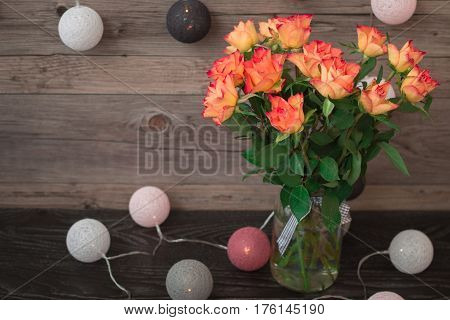 Blooming orange roses on a light gray wooden background and garland in the form of balls, wrapped in colored thread. A beautiful bouquet of roses in vase.