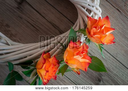 A white grapevine, decorated with beautiful orange roses. Light gray wooden background. Romantic and subtlety.