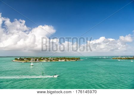 cruise touristic boats or yachts floating by island with houses and green trees on turquoise water and blue cloudy sky yachting and isle life around beautiful Key West Florida USA