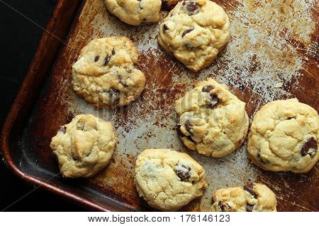 Home made chocolate chip cookies on a tarnished baking sheet