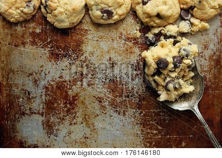 Home made chocolate chip cookies frame a tarnished baking sheet with a vintage spoon filled with dough