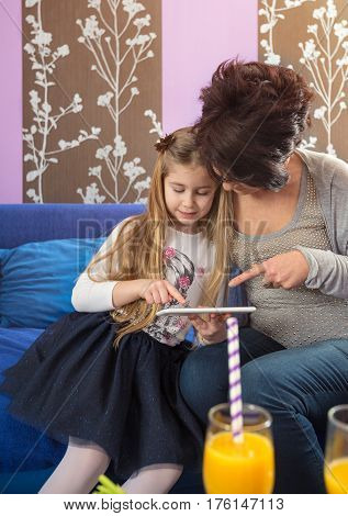 grandma and granddaughter looking at tablet's screen together