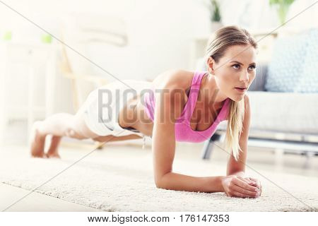 Fit girl in plank position at home in the living room