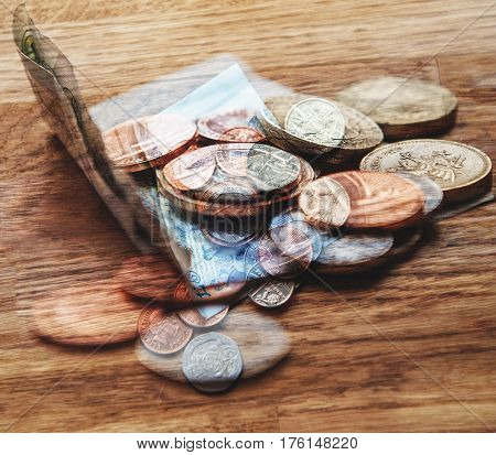 Modern Composite of Pound sterling and coins quids nicker on oak table in luxury restaurant in London. The pound sterling (symbol: £; ISO code: GBP [Great Britain Pound]) commonly known as the pound is the official c