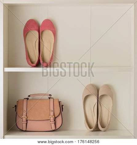 Women's shoes (ballet shoes) and bag in the white wardrobe. Selective focus.