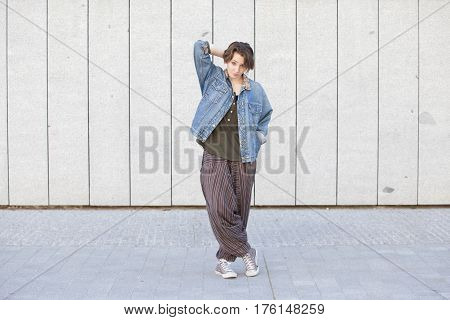 androgynous teen woman wearing trendy jean clothes isolated on a grey wall