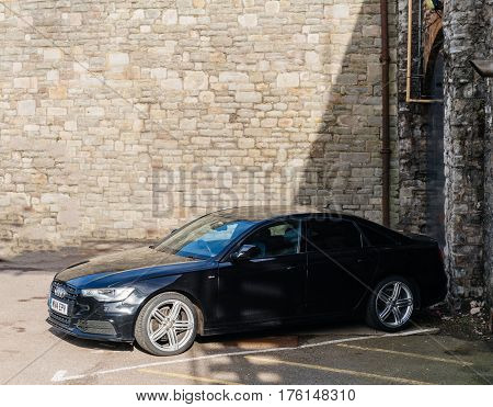 BRISTOL UNITED KINGDOM - MAR 7 2017: Elevated view of luxury Audi A7 limousine in a closed parking surrunded by stone wall
