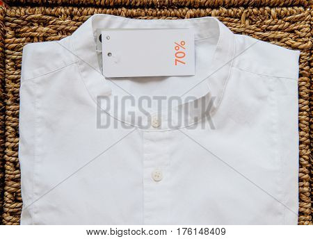 Modern fashion trendy white shirt with 70% reduction price tag on handcrafted wooden background