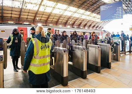 BRISTOL UNITED KINGDOM - MAR 7 2017: Commuters early in the morning using their oyster card and train tickets at the machine at the Bristol Temple Meads railway station with GWR Great Western Railway employee surveilling assisting the crowd