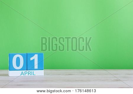 April 1st. Day 1 of month, calendar on wooden table and green background. Spring time, empty space for text.