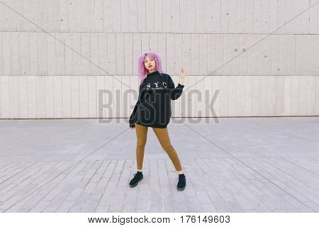 Young woman with purple afro hair and New York style isolated on a wall