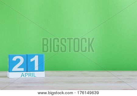 April 21st. Day 21 of month, calendar on wooden table and green background. Spring time, empty space for text.