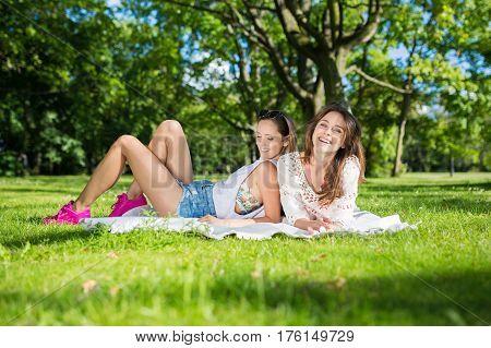 Girls on blanket relaxing in bosom of nature