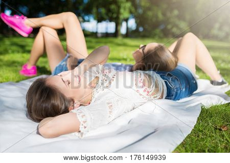 Two Pretty Women Relaxing At Park Listening Music