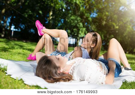 Pretty Happy Women Lying On Blanket In Park