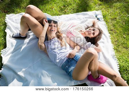 Beautiful Female Friends Relaxing On Blanket In Park Laughing