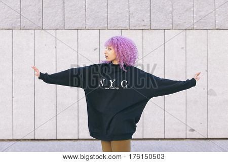 mixed race black woman with purple afro hair and a New York sweater isolated on the street
