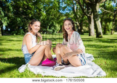 Happy Female Friends Sitting On Blanket In Park