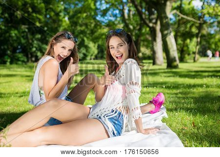 Happy Female Friends Showing Thumbs Up Sitting Outside