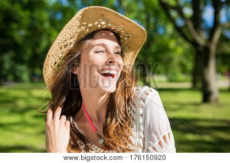 Natural carefree woman in hat laughing loudly