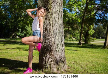 Beautiful girl leaning against tree posing in park