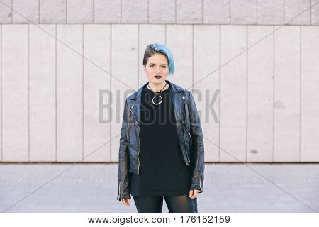young punk woman with blue dyed hair and a leather jacket isolated on the street
