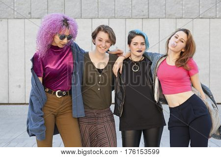 group of adolescence girlsfriends having fun and hugging themselves isolated on the street