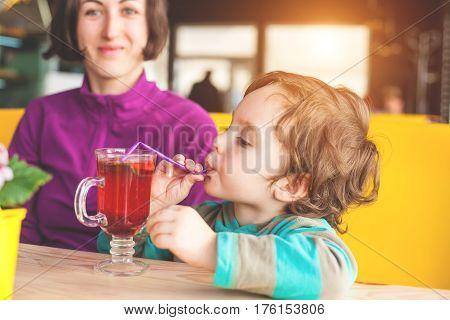 Boy Drinking Through A Straw.