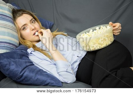 Young pretty blond caucasian woman with light brown eyes lying on sofa eating popcorn. She is watching a movie at home and wearing smart clothes.