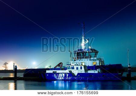 Blue tug ship moored at the pier in Riga Latvia