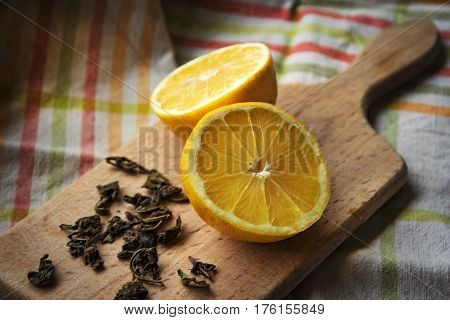 Still life with spill split in half lemon green tea on a wooden board