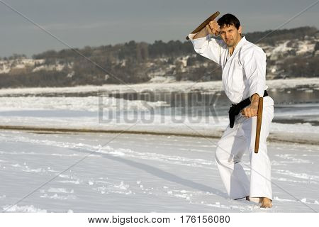 The man in white kimono is practicing japanese martial arts with tonfa in the snow on winter background.