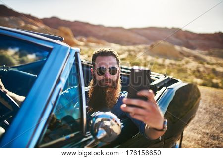 man with beard taking selfie with smartphone in vintage hot rod car