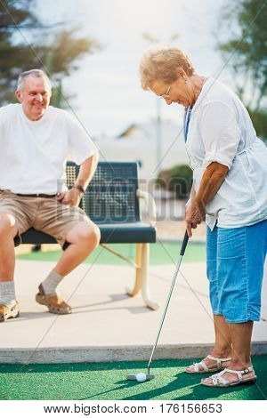 active elderly senior couple playing miniature golf together