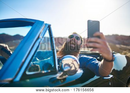 happy guy with beard laughing while taking selfie in vintage car