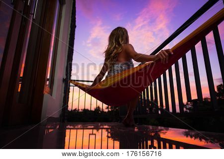 Woman relaxing in the hammock and enjoying sunset from balcony