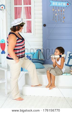 Mother in a white cap with a visor is near a little boy with a life buoy on his neck near the porch of the white house with lilac door and arrow beach
