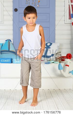A little boy in a white shirt with folded hands in his pockets standing near the porch with an anchor, pillows, bars labeled coast and sea